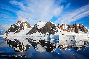 Snow covered peaks of Booth Island and sky reflected in Lemaire Channel, Antarctica. December 2019.  -  Ashley Cooper