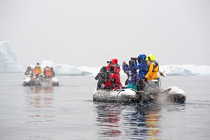 Chinese tourists taking photos from zodaics in heavy snow. Fournier Bay, Antarctica. December 2019.  -  Ashley Cooper