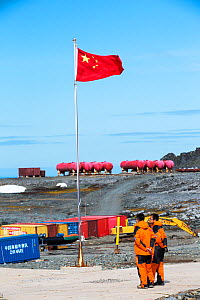 Workers standing near Chinese flag at Great Wall Station, Chinese research base, King George Island, South Shetland Islands, Antarctica. January 2020.  -  Ashley Cooper