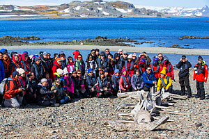 Chinese tourists posing beside Whale skeleton at Great Wall Station, a Chinese research base. King George Island, South Shetland Islands, Antarctica. January 2020.  -  Ashley Cooper