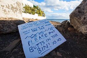 Sign to encourage tourists to throw their cigarette butts in the bin rather than on the beach. Playa Quemada, Lanzarote, Canary Islands, Spain. 2019.  -  Ashley Cooper