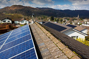 Photovoltaics on roofs of bungalows, hills in background. Ambleside, Lake District National Park, Cumbria, England, UK. March 2020.  -  Ashley Cooper