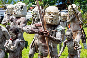 Mudmen, Papuan men in traditional clay masks, bodies painted with clay, boys also painted. At Sing-sing gathering where traditional cultures including dance and music are shared. Morobe Show, Lae, Pap...  -  Konrad Wothe