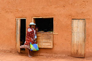 Woman standing outside shop. Central Madagascar. 2019.  -  Terry Whittaker