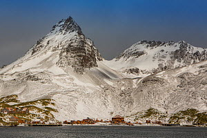 Abandoned buildings of former whaling station below snow covered mountains. Prince Olav Harbour, South Georgia. November 2017.  -  Mark MacEwen