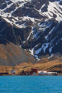 Abandoned whaling station below mountain, Grytviken whaling station was the largest on South Georgia. October 2017.  -  Mark MacEwen