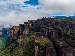 People alongside helicopter with film camera mounted, on tepui table-top mountain, aerial view. Taken on location for BBC Seven Worlds One Planet series. Canaima National Park, Venezuela. 2018.  -  Mark MacEwen