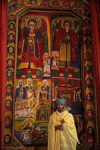 Young priest standing in front of mural paintings in the sanctum of Ura Kidane Mehret, an Ethiopian Orthodox Church. Zege Peninsula, Ethiopia. 2018.  -  Bruno D'Amicis