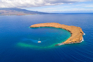 Molokini Crater, aerial shot of the entire crescent shaped islet with one charter sailboat boat and the island of Maui in the background, Hawaii.  -  David Fleetham