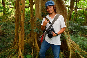 Photographer David Lin, in front of Bayan fig tree, (Ficus benjamina) one single individual tree, Bayan garden protected forest, Kenting National Park, Taiwan  -  Staffan Widstrand / Wild Wonders of China