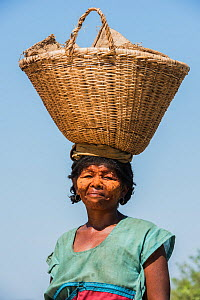 Local woman carrying basket on her head, with sandalwood past on face. South Madagascar. November 2018.  -  Pete Oxford