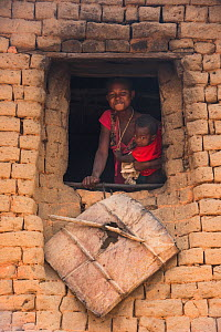 Local people, woman with child looking out of window, Hauts Plateaux, Central Madagascar. November 2018.  -  Pete Oxford