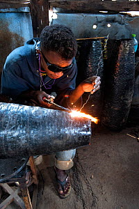 Deaf worker, in metal factory, making metal artefacts for tourist industry, Antananarivo, Madagascar. October 2018.  -  Pete Oxford
