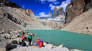 Panning shot showing people gathered near meltwater from retreating glacier flowing over rock into lake, below Torres del Paine towers. Torres del Paine National Park, Patagonia, Chile, January, 2020.  -  Ashley Cooper
