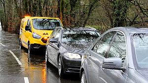 Panning shot of cars and an AA breakdown vehicle at a stand-still next to flood caused by Storm Ciara at Rothay Bridge in Ambleside, Lake District, UK, February, 2020.  -  Ashley Cooper