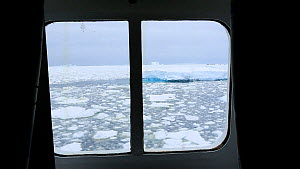 Looking out of a cabin window on an expedition cruise ship onto sea ice in the Lemaire channel between Booth Island and the Kiev Peninsular, Antarctica.  -  Ashley Cooper