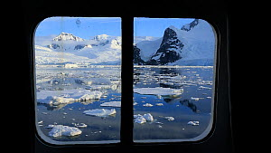 Looking out of a cabin window on an expedition cruise ship onto the Lemaire channel between Booth Island and the Kiev Peninsular, Antarctica.  -  Ashley Cooper