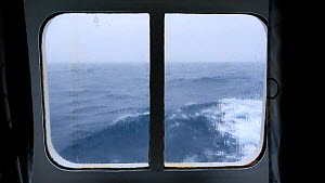 Waves moving outside a cabin window on an expedition cruise ship crossing the Drake Passage between Antarctica and South America.  -  Ashley Cooper
