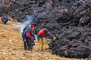 Group of tourists are grilling marshmallows on lava flow, Fagradalsfjall volcano, Iceland. Although many people are doing this, it is not entirely without risk, especially in areas with large lava tow...  -  Theo  Bosboom