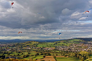 Paragliders flying from Selsley Hill, with Stroud and Gloucester in the background, Gloucestershire, UK, October.  -  Nick Upton