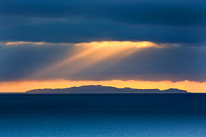 View of Sante Fe from San Cristobal, with sun rays over the sea, Galapagos  -  Maxime Aliaga