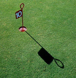 Number 10 marker, hole and long shadow in close mown grass turf of a golf practice putting green, Surrey, October  -  Nigel Cattlin