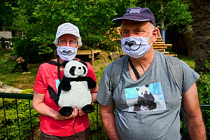 French tourists who love Giant pandas (Ailuropoda melanoleuca) with panda T-shirts, facemasks, caps and backpacks. Beauval ZooParc, Saint-Aignan, France. Model released. August 2021. Editorial use onl...  -  Eric Baccega