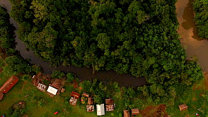 Aerial shot moving over river and rainforest to reveal a village in rainforest clearing, Maijuna Indigenous Community, Sucusari River, Rio Napo, Loreto, Peru.  -  Mark Bowler
