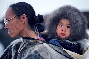 Inuit grandmother, Patdlunguaq,carring Peter in a sealskin Amaut (hooded jacket). Qeqertat, Northwest Greenland. (1980)  -  Bryan and Cherry Alexander