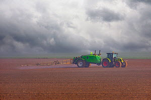 Spraying chemicals onto field using a wide farm sprayer behind a tractor, Oise, France. April  -  Sylvain Cordier