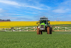Spraying chemicals onto crops using a wide farm sprayer behind a tractor, Oise, France. April  -  Sylvain Cordier
