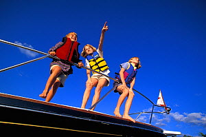 Children on deck of powerboat wearing life jackets, looking and pointing upwards.  -  Onne van der Wal