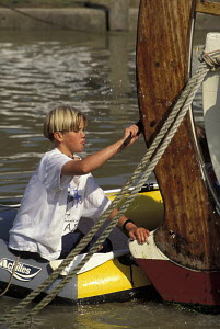 Boy cleaning the varnished rudder or a wooden boat from a rubber dinghy, Rye Harbour, East Sussex, England 1996. - Gary John Norman