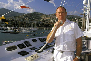 The captain of a superyacht uses the VHF radio to communicate from the bridge. Antibes, France 1998. - Gary John Norman