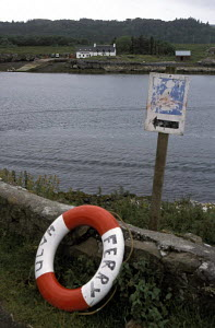 Ulva ferry life ring leaning against wood with the small island of Ulva across the water, off the coast of the Isle of Mull, Western Isles, Scotland, UK - Daniel Allisy