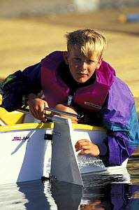 Young boy mounting the rudder in an Optimist dinghy during training in Florida, USA - Onne van der Wal