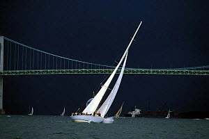 Storm clouds over the 12 Metre yacht ^Columbia^ as she sails under the Newport Bridge during the Museum of Yachting Regatta, Rhode Island, USA  -  Onne van der Wal