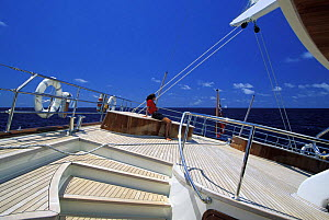"""A crew member relaxing on the deck of the 170ft Perini Navi superyacht """"Liberty"""".  -  Onne van der Wal"""