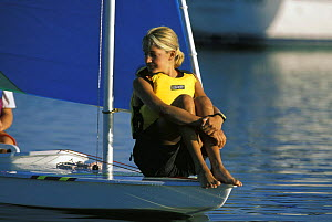 Girl balancing on the bow of a Sunfish dinghy, sailing in the early morning calm off Cape Cod, USA  -  Onne van der Wal