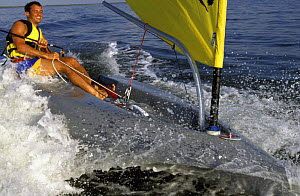 Man sailing a plastic roto moulded Escape dinghy. Model Released and Property Released.^^^ These boats are aimed at beginners and provide an inexpensive solution to getting children out on the water.  -  Onne van der Wal