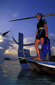 Woman with snorkeling gear standing on stern of a dhoni, the typical Maldivian boat, Maldives. Model released.  -  Roberto Rinaldi