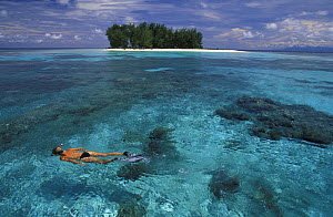 Snorkeling in clear waters off small and uninhabited Dondola Island, Togian Islands, Sulawesi, Indonesia. Model released. - Roberto Rinaldi