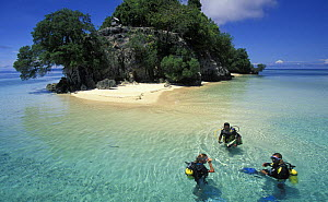 Three divers in the clear waters in front of Punten Kramat, Walea Island, Sulawesi, Indonesia  -  Roberto Rinaldi