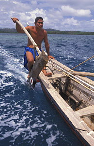 Man on a popow, the traditional outrigger canoe used on Yap, Micronesia. A long pointed paddle is held overboard in the wake of the canoe to act as a rudder. - Roberto Rinaldi