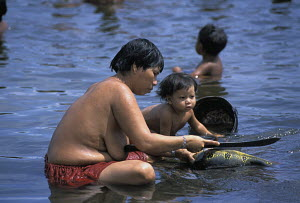 """A Yanomami lady with her child, preparing food  on the Casiquiare River, Amazon, Brazil, 2001. During Sir Peter Blake's """"Seamaster"""" expedition. - Franck Socha"""