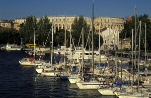 Boats moored in marina with amphitheatre in the background, Pula, Slovenia. - James Boyd