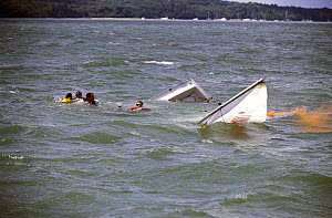 Crew of a sinking Sonar have activated an orange flare and wait to be rescued after their keelboat was overcome by waves during racing at Cowes Week, UK, 2001.  -  Rick Tomlinson