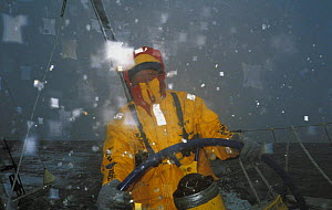"""Helmsman in waterproofs as """"Intrum Justitia"""" passes through the Southern Ocean in the Whitbread Round the World Race, skippered by Lawrie Smith, 1993-94. ^^^The team won the second leg of the race and...  -  Rick Tomlinson"""
