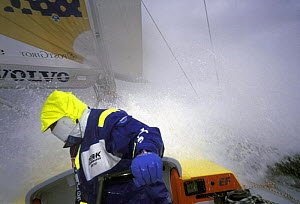 Crew member aboard ^EF Language^ faces away from the spray on the deck in the Southern Ocean during the Whitbread Round the World Race, 1997-1998.  -  Rick Tomlinson