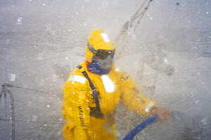 """Helmsman on """"Intrum Justitia"""" is geared up in waterproofs and goggles as they move through the Southern Ocean in the Whitbread Round the World Race, 1993.  -  Rick Tomlinson"""